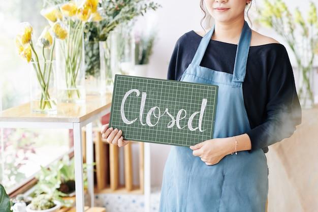 Proprietário da loja segurando placa fechada