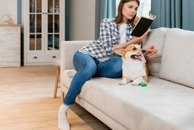 Proprietário de cachorro e mulher lendo um livro no sofá