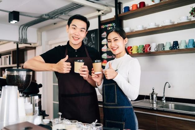 Proprietário de café barista jovem masculino e feminino em pé dentro do balcão do café.