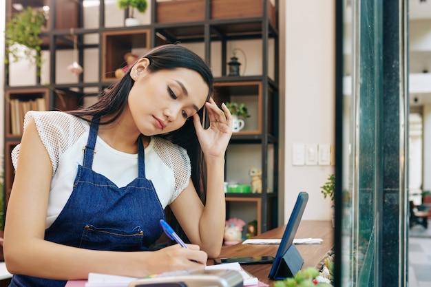 Proprietário de café entediado e cansado preenchendo documentos após terminar o trabalho à noite