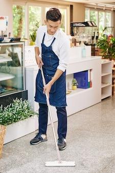 Proprietário de cafeteria limpando chão