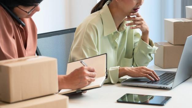 Proprietário de casal de negócios asiáticos trabalhando em casa com a caixa de embalagem de sua loja online, prepara-se para entregar produtos aos clientes, conceito de estilo de vida da geração alfa.