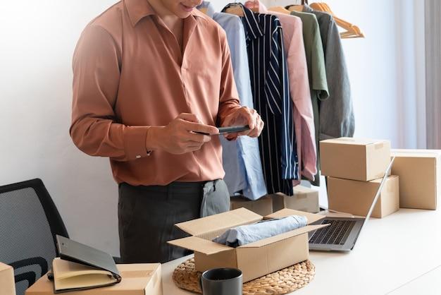 Proprietário de empresa asiática trabalhando em casa com a caixa de embalagem de sua loja online se prepara para entregar produtos