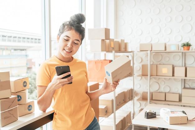 Proprietário de empresa de mulheres asiáticas trabalhando em casa com caixa de embalagem no local de trabalho - empreendedor de pequenas e médias empresas de compras online ou conceito de trabalho freelance