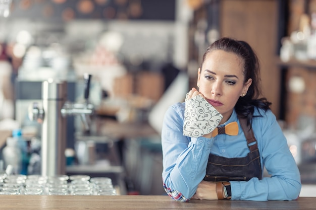 Proprietário de empresa feminina triste segura a máscara facial na mão e se inclina contra o bar em seu café vazio.