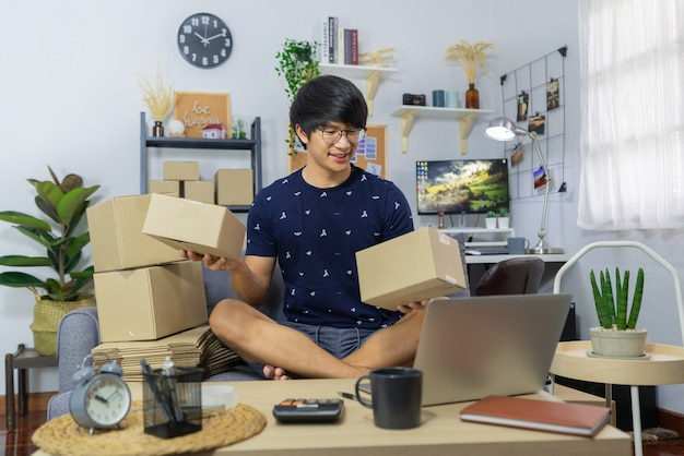 Proprietário de empresa homem asiático ou venda de mercadorias on-line e preparar caixa de embalagem de papelão de embalagem de produto