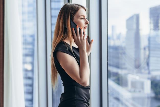 Proprietário de empresa jovem elegante segurando documentos falando no celular, discutindo as condições do contrato em pé no escritório.