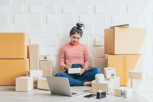 Proprietário de empresa mulher asiática trabalhando em casa com caixa de embalagem no local de trabalho