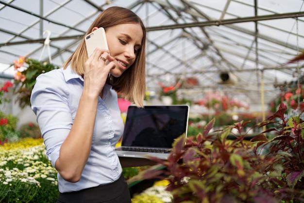 Proprietário de estufa sorridente posando com um laptop nas mãos, falando ao telefone, tendo muitas flores e telhado de vidro.