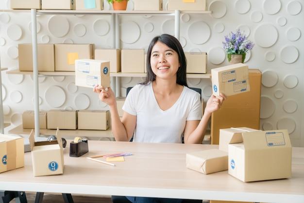 Proprietário de negócios de mulheres asiáticas trabalhando em casa com a caixa de embalagem no local de trabalho
