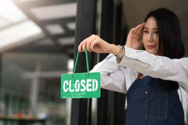 Proprietário de pequena empresa de mulher segurando uma placa de fechado em um café.