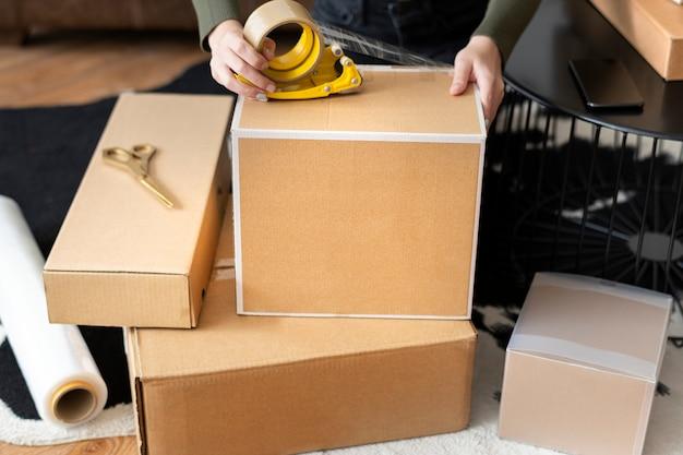 Proprietário de pequena empresa embalando caixas de pacotes de produtos para entrega