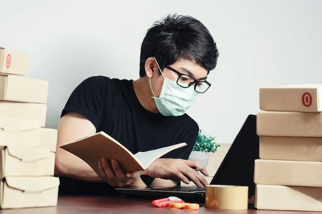 Proprietário de pequena empresa homem asiático trabalhe em casa e use uma máscara para se proteger contra o vírus corona. marketing online, conceito de startup pme.