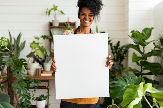 Proprietário de pequena empresa segurando um cartaz em branco