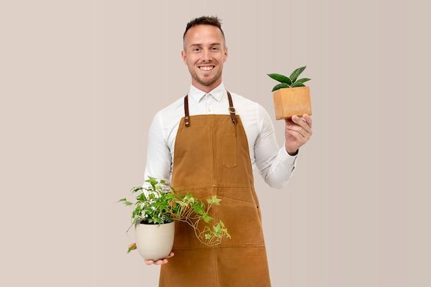 Proprietário de pequena empresa segurando vasos de plantas