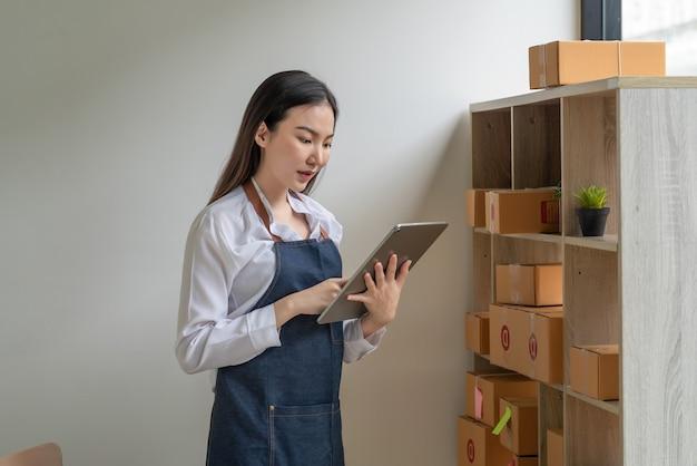 Proprietário de pequena empresa vestindo um avental em pé segurando um tablet uma caixa de pacote no chão em casa.
