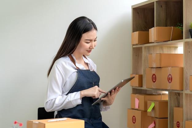 Proprietário de uma pequena empresa jovem asiática está vendendo on-line segurando um tablet com caixa de pacote na prateleira em casa.
