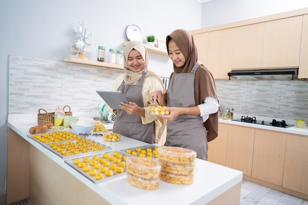Proprietário de uma pequena empresa muçulmana que faz um lanche caseiro de nastar para vender. linda mulher asiática com parceiro cozinhando e segurando o tablet pc