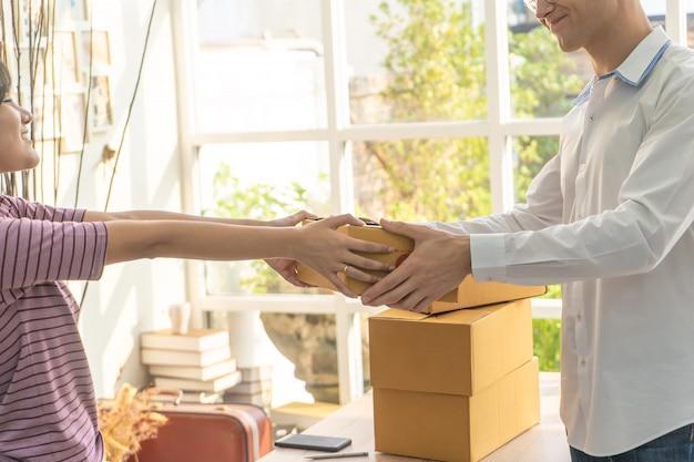 Proprietário do negócio home do vendedor fêmea que segura o pacote ao cliente