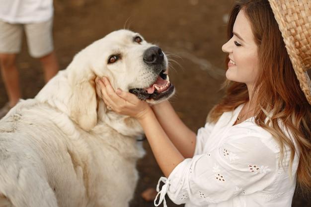 Proprietário e cão labrador retriever em um quintal. mulher de vestido branco. golden retriever.