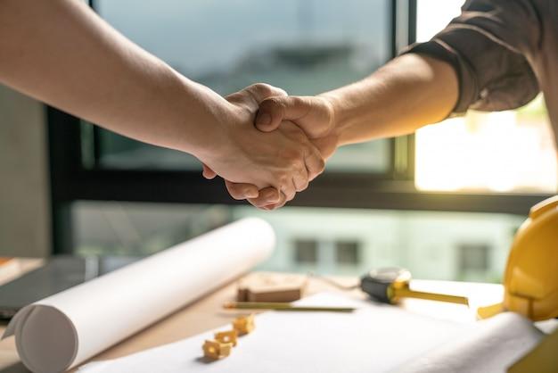 Proprietário e construtor está de acordo e apertar as mãos para comemorar no sucesso do acabamento no projeto de construção de contrato de construção de casa