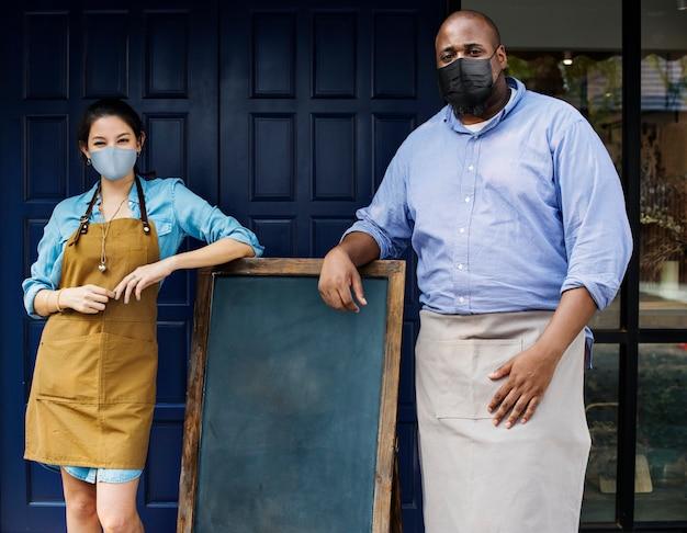 Proprietários de empresas usando máscara facial em um café