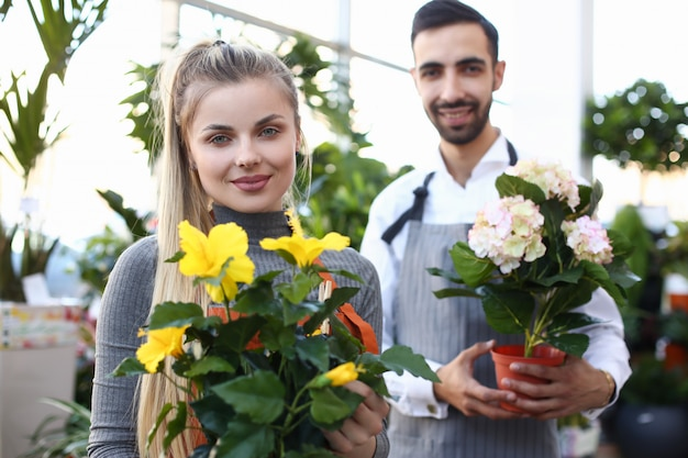 Proprietários de lojas de flores, segurando lindas plantas de casa com flores