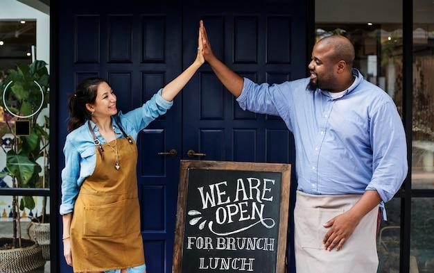Proprietários de negócios alegre permanente com lousa aberta