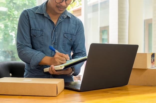 Proprietários do negócio das pme que verificam o inventário com o portátil na tabela.