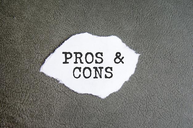Prós e contras assinam no papel rasgado no fundo cinza, conceito de negócio
