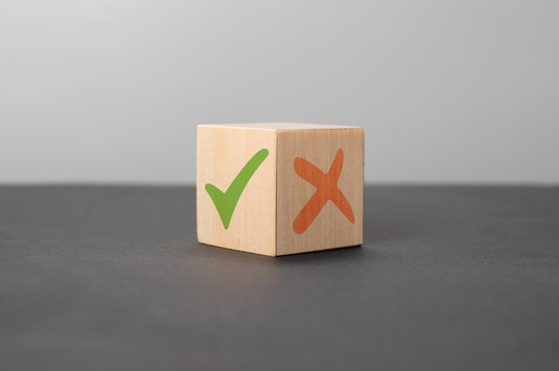 Prós e contras conceito de cubo de madeira com uma marca de seleção verde e uma cruz vermelha