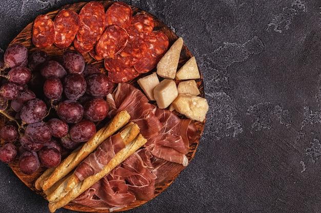 Prosciutto, linguiça, vinho, uva, parmesão na mesa escura