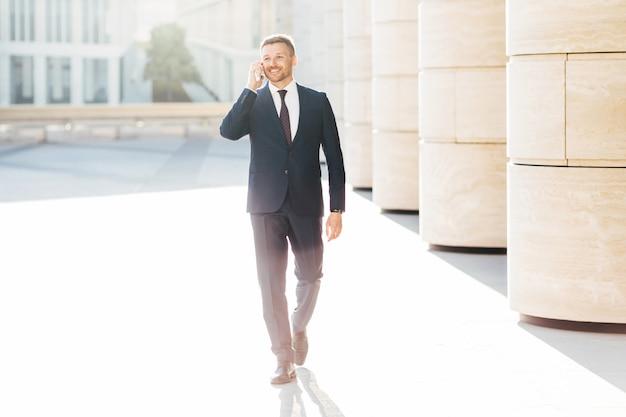 Próspero empresário masculino em traje formal, tem conversa por telefone com o parceiro de negócios