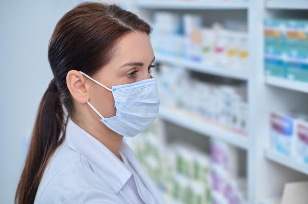 Proteção contra o vírus. mulher adulta jovem pensativa de cabelos escuros usando máscara protetora e jaleco branco em pé na sala iluminada da farmácia