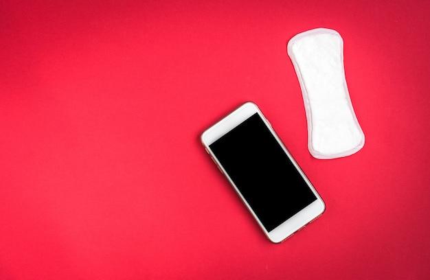 Proteção da higiene da mulher ou absorventes higiênicos com pétalas de rosa e telefone móvel sobre fundo vermelho. rastreamento do ciclo menstrual.