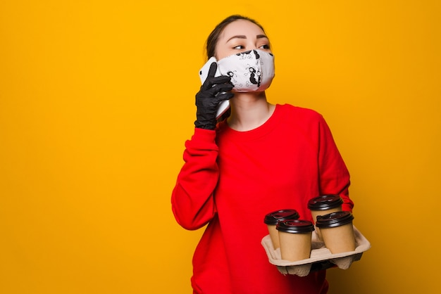 Proteção da saúde, segurança e conceito de pandemia. mulher asiática entregadora falando ao telefone com máscara protetora e luvas