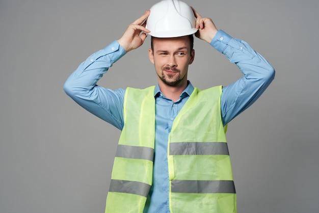Proteção de colete reflexivo de homem trabalhando fundo claro