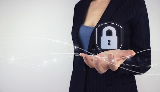 Proteção de dados, conceito de segurança cibernética. mão segure o cadeado de segurança do ícone do holograma digital com proteção de dados em fundo cinza. proteção de rede empresarial e dados digitais.