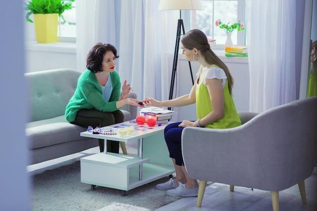Proteção do mal. mulher jovem e bonita tocando um amuleto mágico enquanto está sentada em frente à cartomante