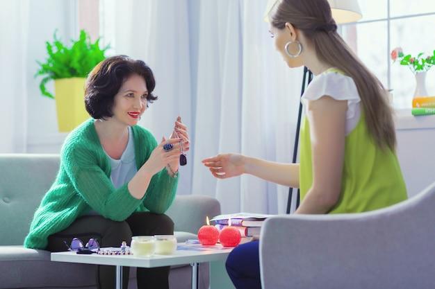 Proteção poderosa. mulher amigável e positiva segurando um amuleto especial enquanto o dá para seu cliente