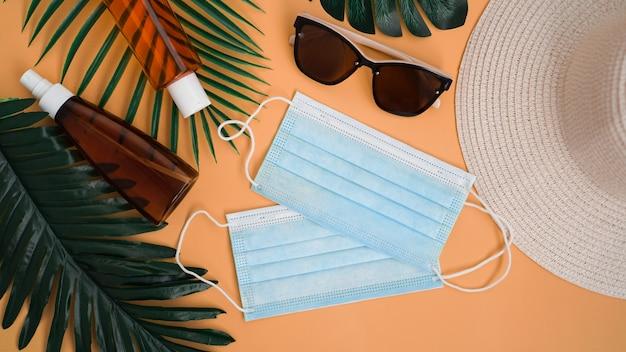 Proteção solar. chapéu de palha de praia, óculos escuros, creme protetor spf, máscara médica. acessório de praia. viagem de verão no conceito de quarentena de coronavírus
