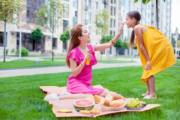 Proteção solar. mulher simpática e positiva segurando um frasco com protetor solar enquanto o coloca no rosto da filha