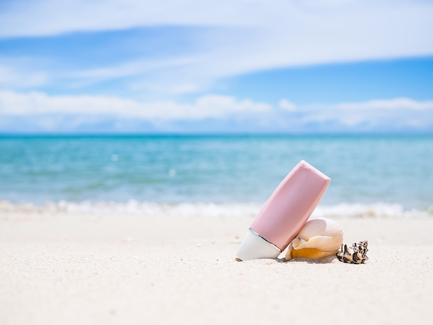 Proteção solar uv a, uv b. com concha do mar na praia de areia e imagem borrada do mar.