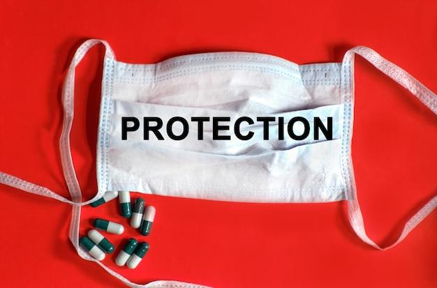 Proteção - texto em uma máscara protetora, comprimidos em um fundo vermelho