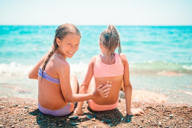 Proteção uv. irmã passa protetor solar no nariz da irmãzinha