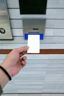 Protegendo o elevador ou o controle de acesso do elevador, a mão do homem está segurando uma configuração de cartão-chave para inserir no suporte do cartão para destravar as portas do elevador antes de subir ou descer.
