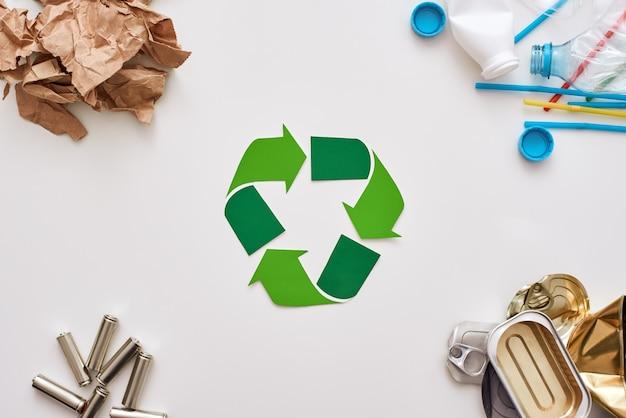 Proteja o meio ambiente. diferentes tipos de lixo. pilhas, latas, papel e plástico nos cantos com papel reciclado no centro
