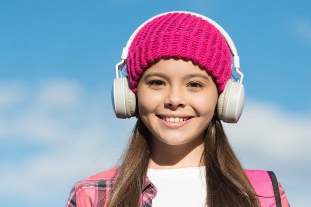 Proteja os ouvidos do seu filho. garota feliz usa fones de ouvido no céu azul ensolarado. criança ouvir música em fones de ouvido. ouvido e cuidados auditivos. vida moderna. nova tecnologia. mantenha você entretido e seguro.