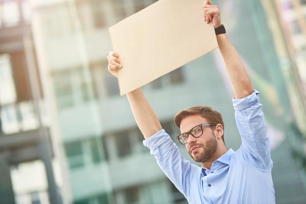Protestando ao ar livre, o retrato de um jovem ativista vestindo camisa azul e óculos segurando