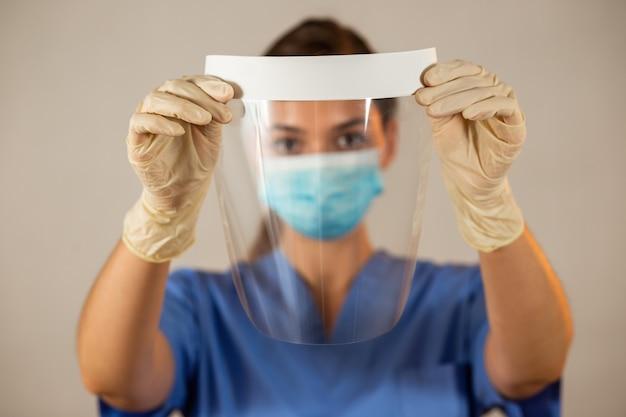Protetor facial nas mãos com luvas de borracha na frente de uma cabeça de enfermeira borrada